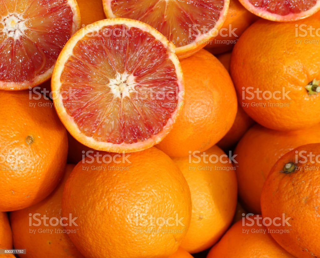 Ripe oranges and an orange cut in the stall of greengrocer stock photo