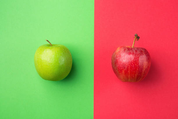 Ripe Organic Apples on Split Duotone Green Scarlet Red Background. Styled Creative Image. Vitamins Summer Vegan Fashion Concept. Food Poster with Copy Space stock photo