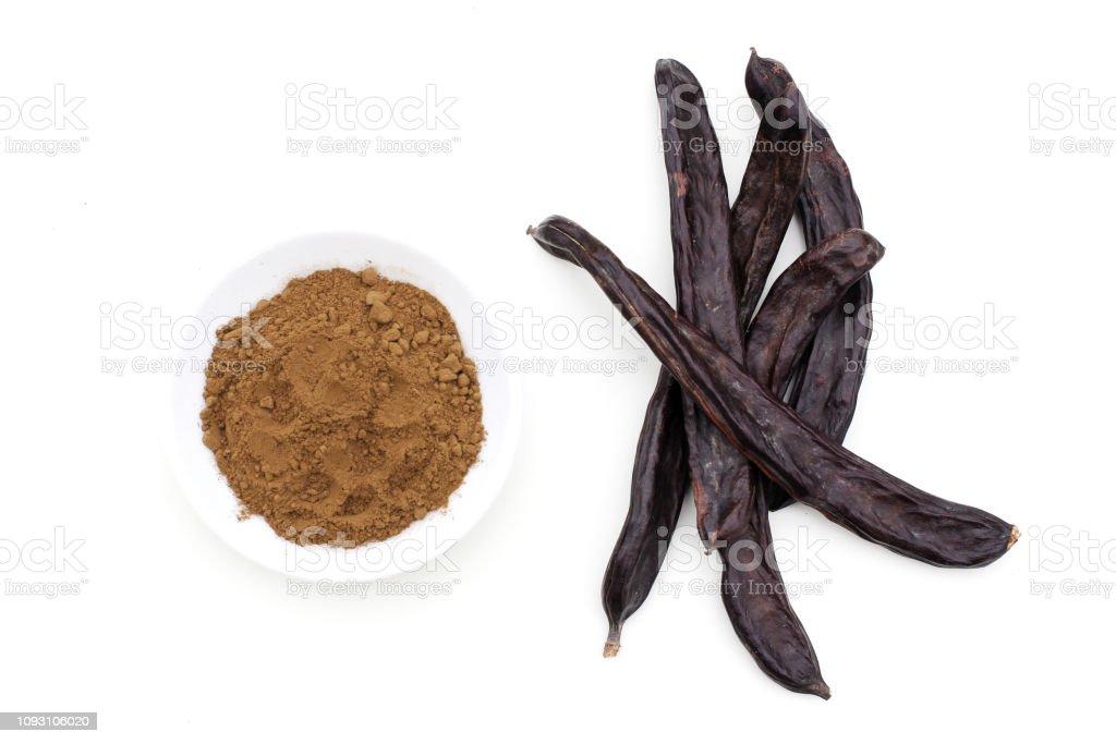 Vainas de algarroba orgánica madura fruta y polvo de algarrobas en fondo blanco. Alternativa saludable a cacao y azúcar. - foto de stock