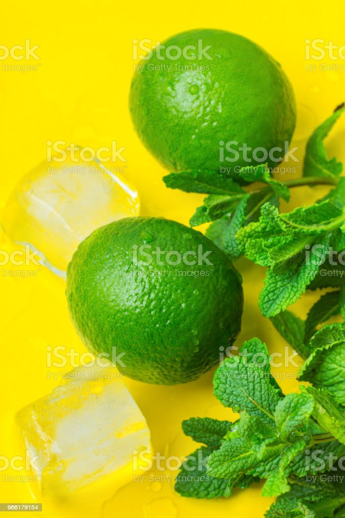 Ripe Organic Limes Fresh Mint Twigs Melted Ice Cubes on Yellow Background with Water Drops. Mojito Cocktail Ingredients. Vibrant Colors Funky Style. Summer Freshness Concept. Copy Space stock photo