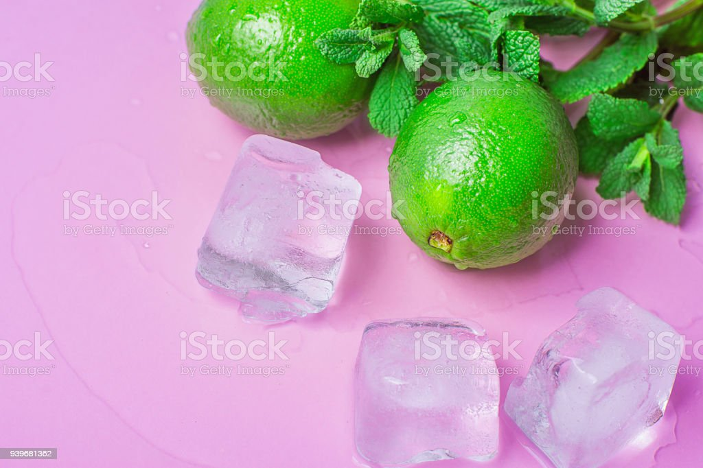 Ripe Organic Limes Fresh Spearmint Melted Ice Cubes on Light Fuchsia Pink Background with Water Drops. Mojito Cocktail Ingredients. Vibrant Colors Funky Style. Summer Freshness Concept. Copy Space stock photo