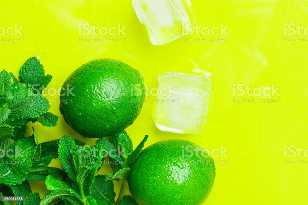 Ripe Organic Limes Fresh Spearmint Melted Ice Cubes on Yellow Background with Water Drops. Mojito Cocktail Ingredients. Vibrant Colors Funky Style. Summer Freshness Concept. Copy Space stock photo