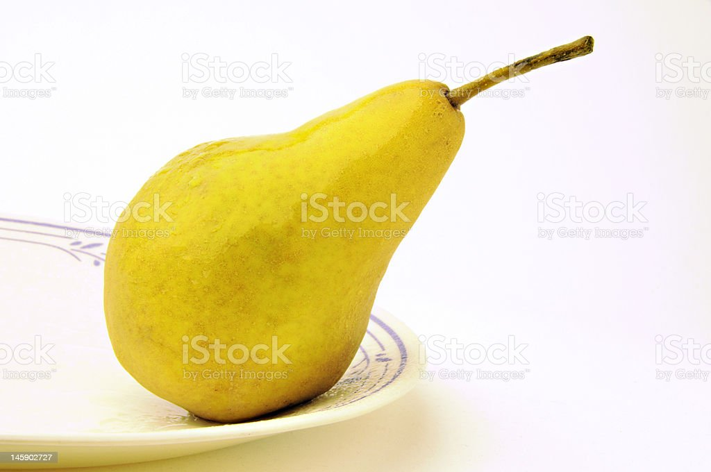 Ripe organic pear on white plate. royalty-free stock photo