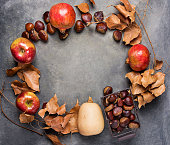 istock Ripe Organic Red Glossy Apples Pomegranates Chestnuts in Wicker Basket Dry Autumn Leaves Arranged in Circle on Dark Stone Background Thanksgiving Fall Abundance Gratefulness. Copy Space 865338670