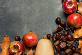 istock Ripe Organic Red Glossy Apples Pomegranates Chestnuts in Wicker Basket Dry Autumn Leaves Scattered on Dark Stone Background. Border Frame. Thanksgiving Fall Abundance Gratefulness. Copy Space 865338690