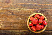 ripe organic strawberry in a wooden plate on a wooden background, space for text