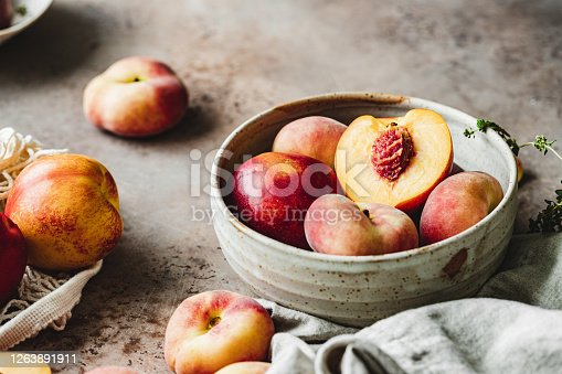 Close-up of ripe peaches in a bowl on kitchen counter.