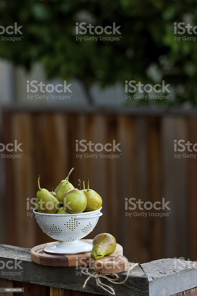 Ripe pears in white colander on wooden surface. royalty-free stock photo