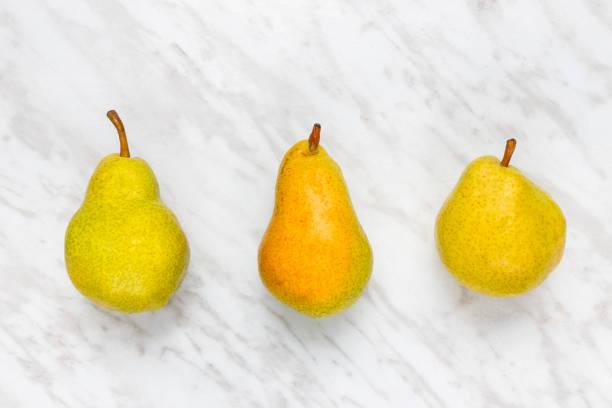 Ripe pears on marble background stock photo