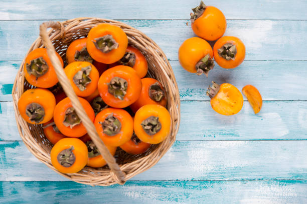 ripe persimmons in wicker basket on wooden table - diospiro imagens e fotografias de stock