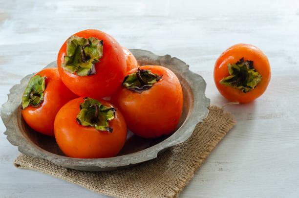 reife kaki - sharonfrucht stock-fotos und bilder