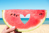 Ripe piece of watermelon with heart shape hole in female hands on the background of the beach on a hot summer day. Concept
