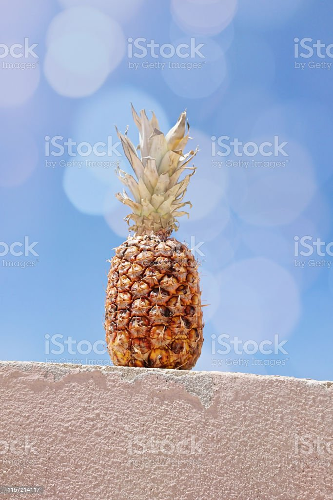 Funny ripe pineapple against blue sky with colored bokeh. Summer...