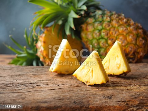 Ripe pineapple fruit cut in a triangle shape on rustic wooden table for high fiber fruits concept.