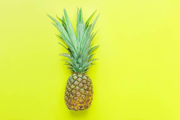 reifer ananas mit langen buschigen grünen blätter auf gelbem hintergrund. sommer urlaub reisen tropische früchte vitamine modekonzept. flache laien textfreiraum - neon partylebensmittel stock-fotos und bilder