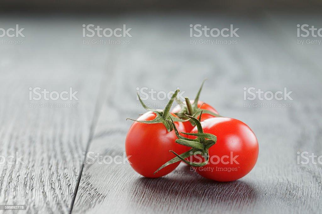 ripe plum tomatoes on wood table stock photo