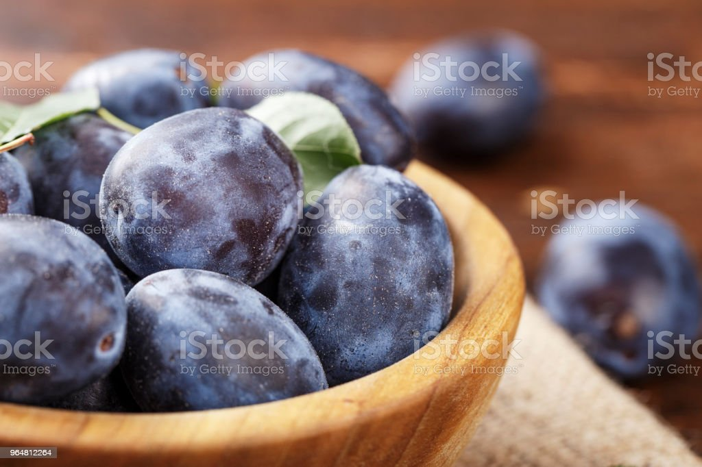 ripe plums in a wooden plate, with leaves royalty-free stock photo