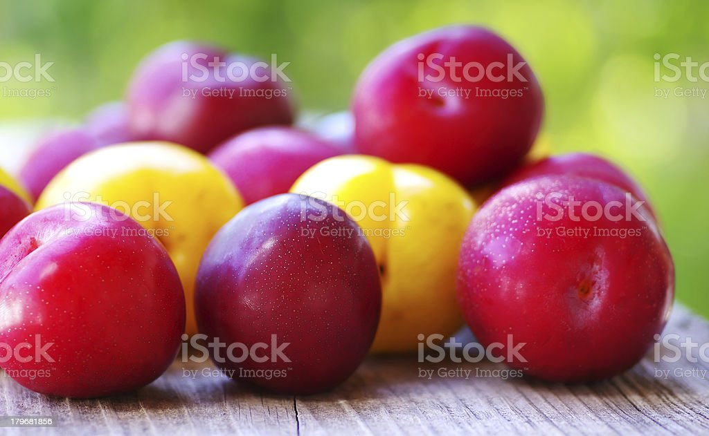 Ripe plums on wooden table royalty-free stock photo