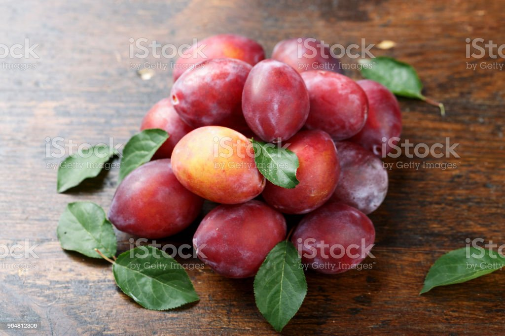 ripe plums with leaves royalty-free stock photo