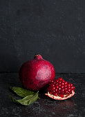 Ripe pomegranates on table against dark background. Space for text