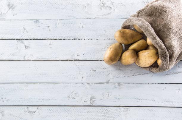 熟土豆在粗麻布麻袋自由地躺在木板上。 - 薯仔食品 個照片及圖片檔