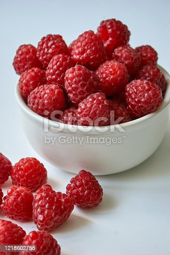 Red raspberries in a white plate.