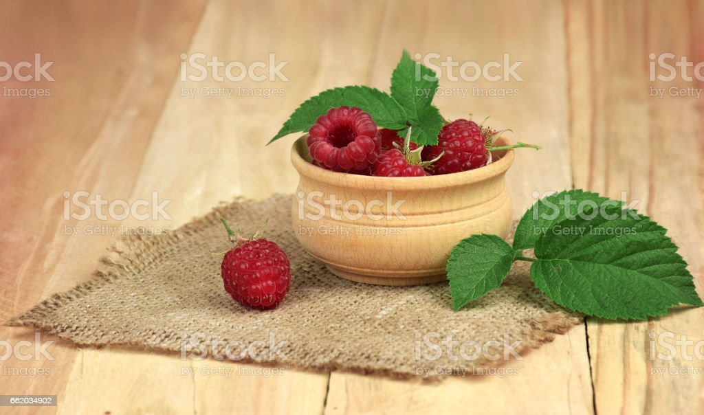 Ripe raspberries with leaves in a bowl on wooden background. royalty-free stock photo