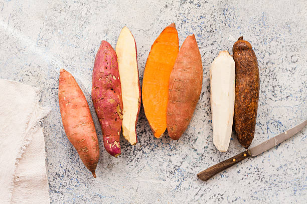 Ripe Raw Sweet Potatoes Displayed On Marble Table stock photo
