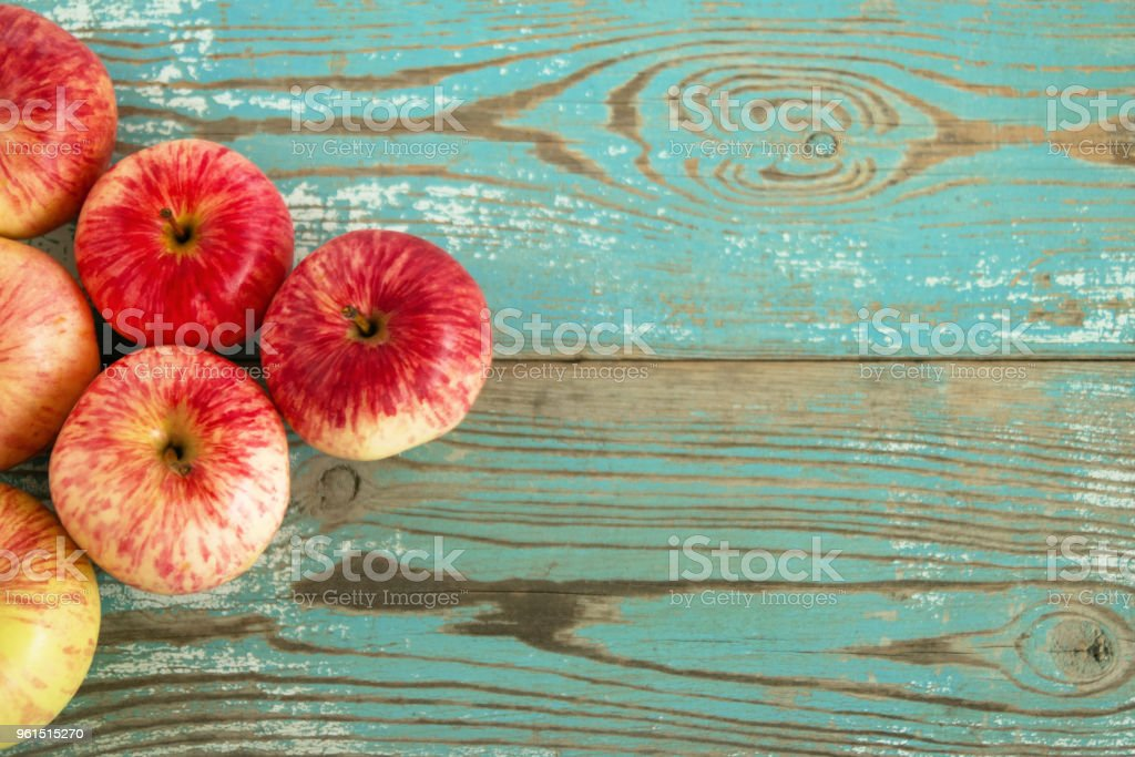 Ripe red and yellow apples on the left side on the turquoise wooden background, top view. stock photo