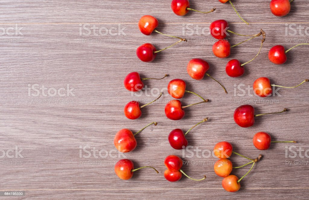 Ripe red and yellow cherries lie on a wooden background. royalty-free stock photo