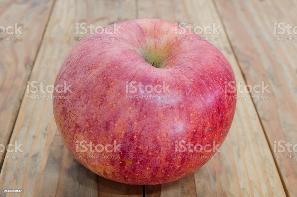 Ripe red apple. Put on a wooden table stock photo