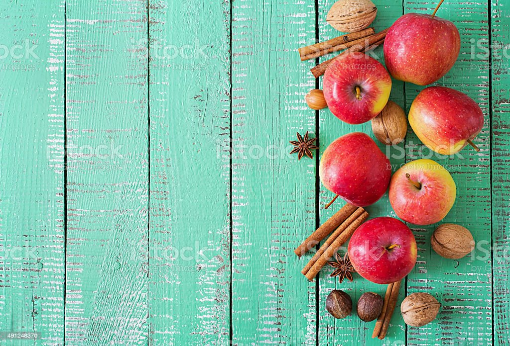 Ripe red apples and spices on a bright wooden background stock photo