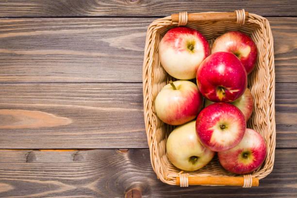 Tahta bir masanın üzerindeki sepette olgun kırmızı elmalar. Üstte görüntü stok fotoğrafı