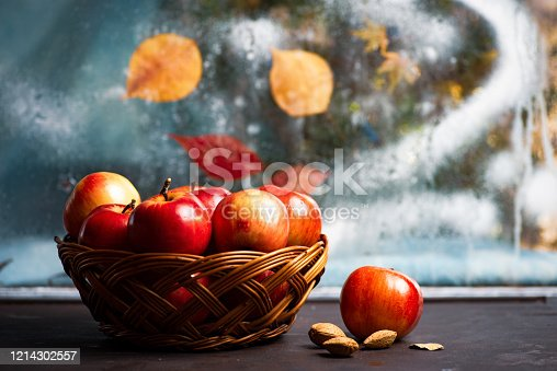 Ripe red apples in wicker basket on a kitchen table by the window