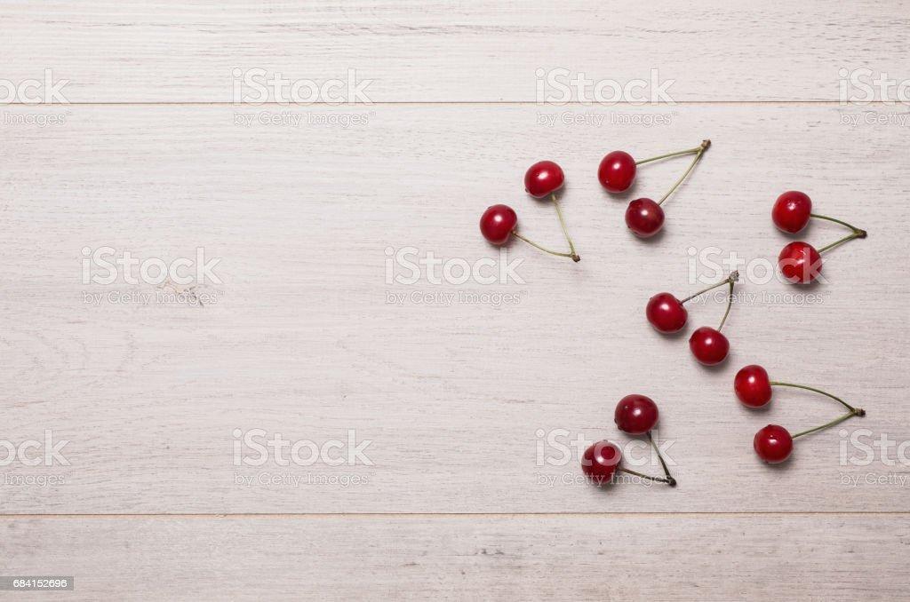 Ripe red cherries lie on a light wooden background. zbiór zdjęć royalty-free