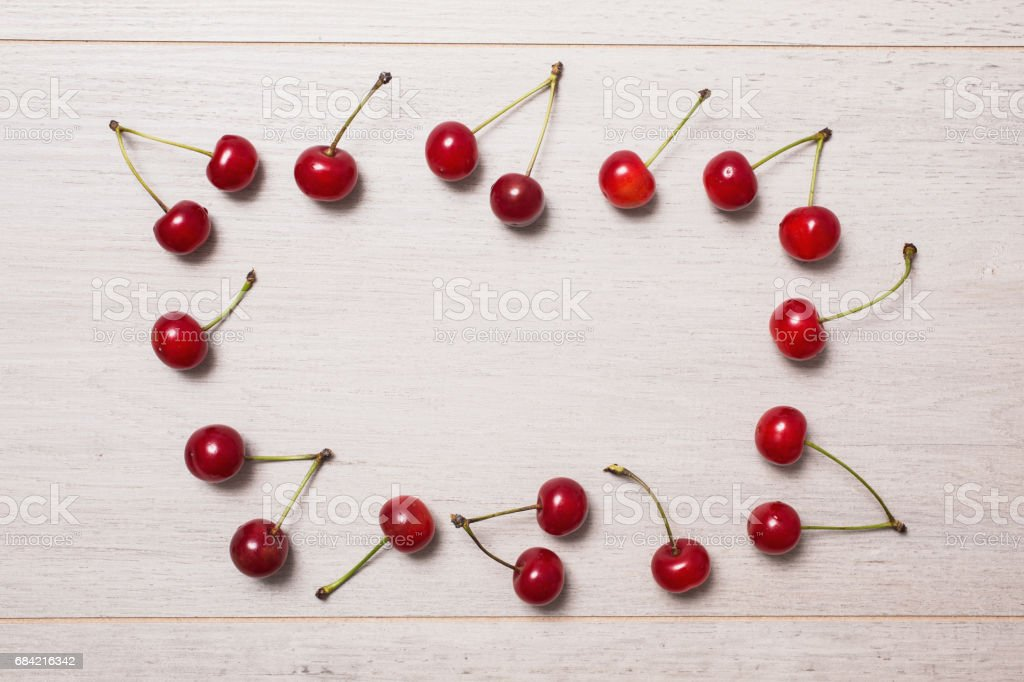 Ripe red cherries lie on a wooden background. Frame of ripe summer berries. Space for text, copyspace royalty-free stock photo