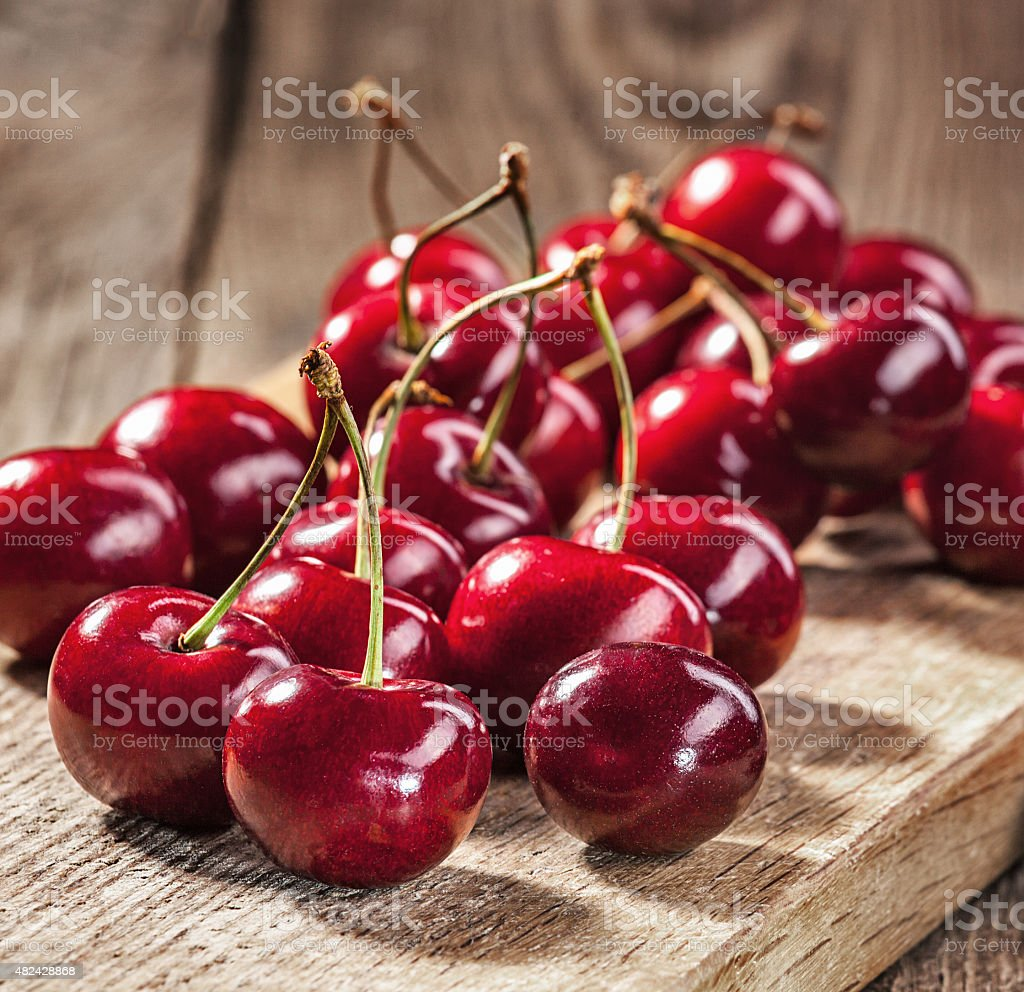 Ripe red cherries on old boards stock photo