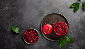 ripe red pomegranate and green leaves on a dark concrete background. copy space, horizontal image