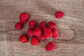 Ripe red raspberries on wooden background