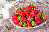 White plate with ripe red rstrawberries and mug with milk on a rustic towel