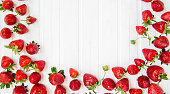 Ripe red strawberries scattered on a white wooden table. Background with strawberries, place for text.