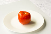 A ripe red tomato with water drops isolated on a white background.