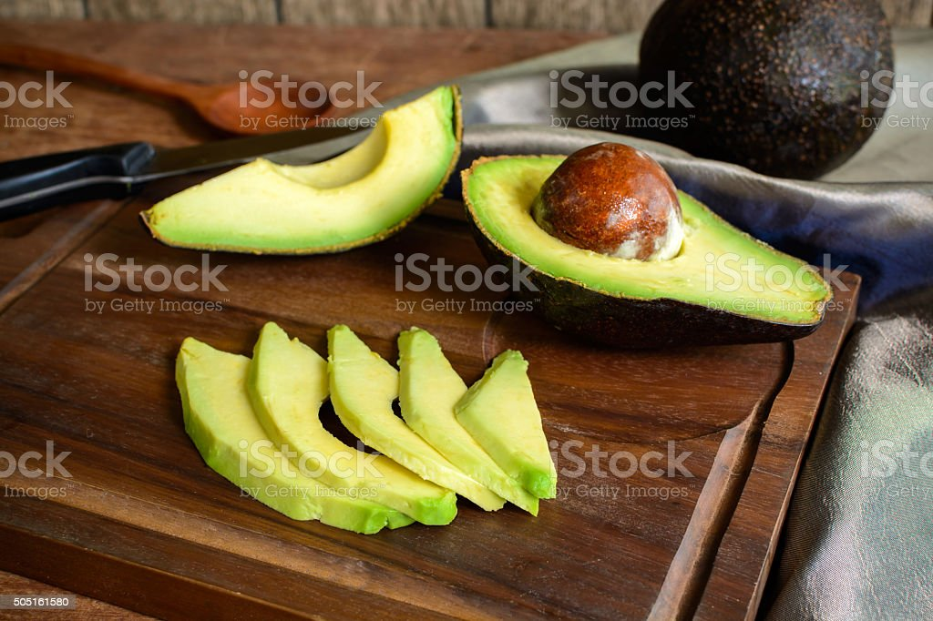 Ripe slice avocado on wooden cutting board stock photo