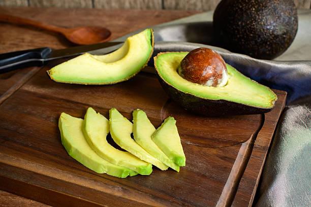 Ripe slice avocado on wooden cutting board stock photo