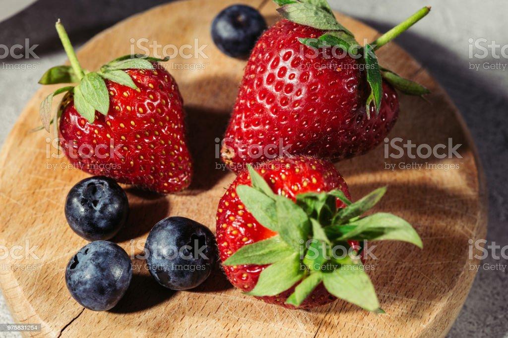Reife Erdbeeren und Heidelbeeren auf Holzbrett - Lizenzfrei Amerikanische Heidelbeere Stock-Foto