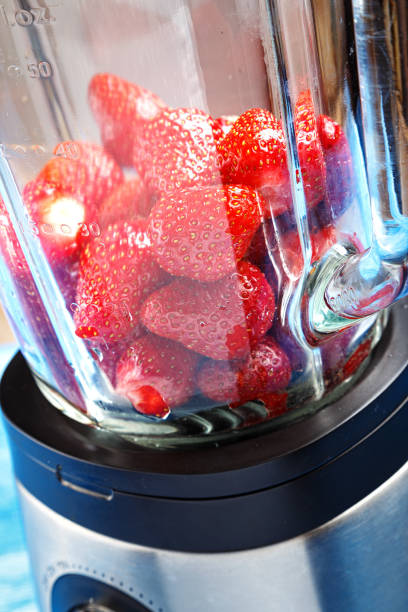 ripe strawberries in a blender stock photo