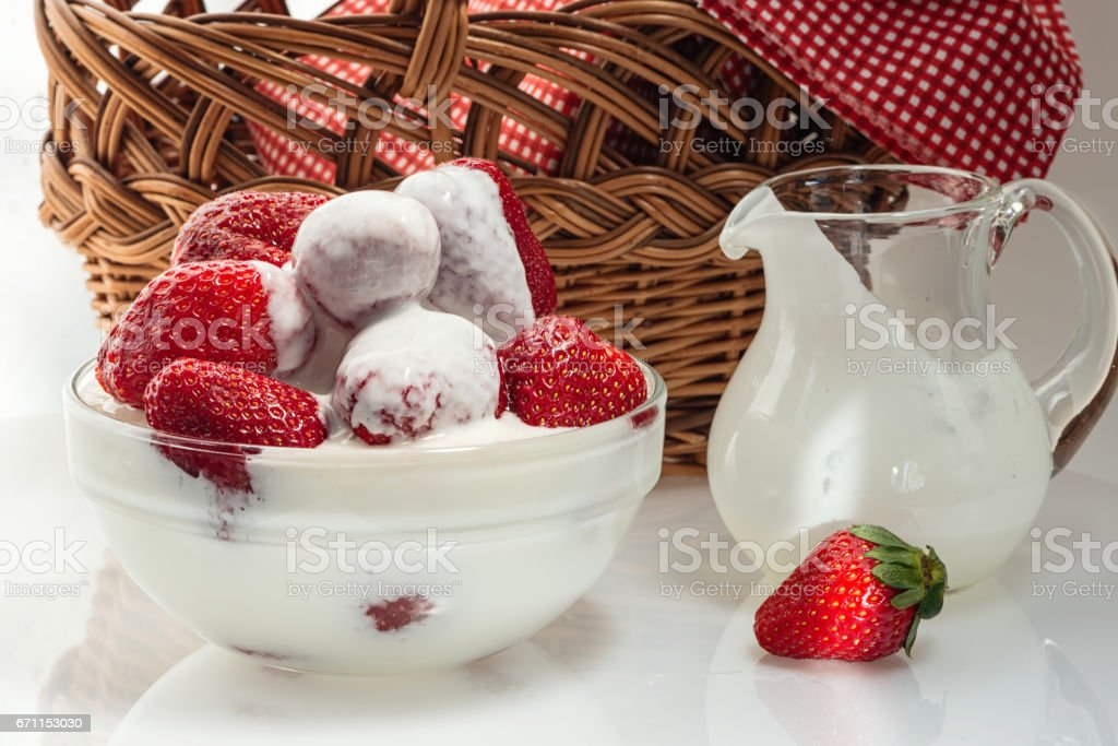 Ripe strawberries in a cup with milk cream стоковое фото