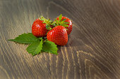 Ripe strawberries on wooden table. Ripe red strawberries. Top view. Three strawberries on a wooden table