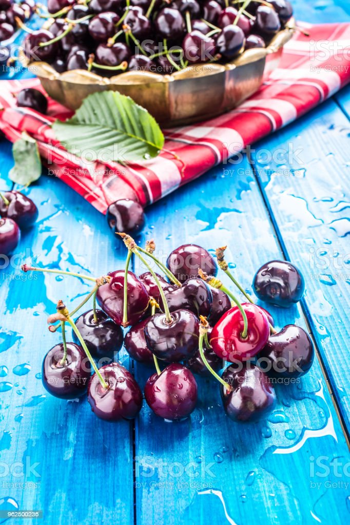 Ripe sweet cherries on blue woden table with water drops - Royalty-free Agriculture Stock Photo