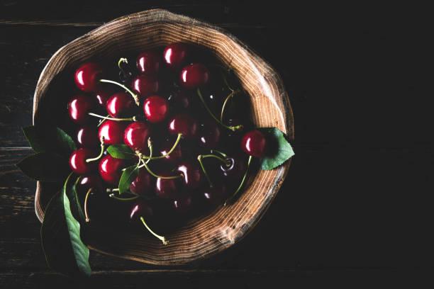 cerezas maduras en madera tazón de fondo oscuro - cereza fotografías e imágenes de stock